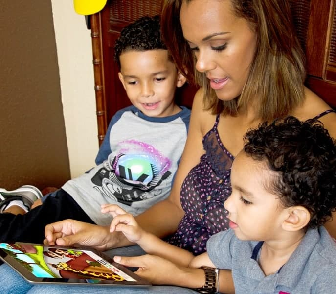 Parent teaching their two children using BookLingual book-based Spanish learning program.